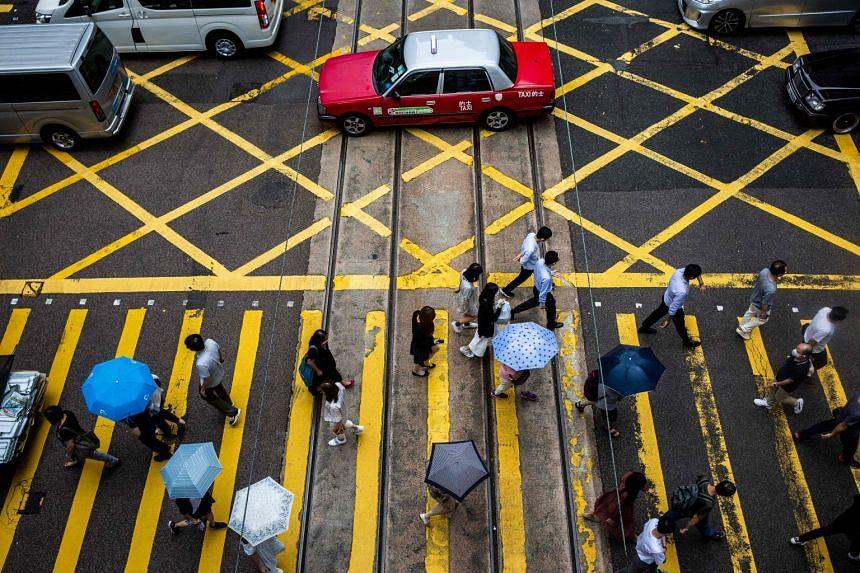 Pedestrians cross a road in Hong Kong on July 16, 2021.