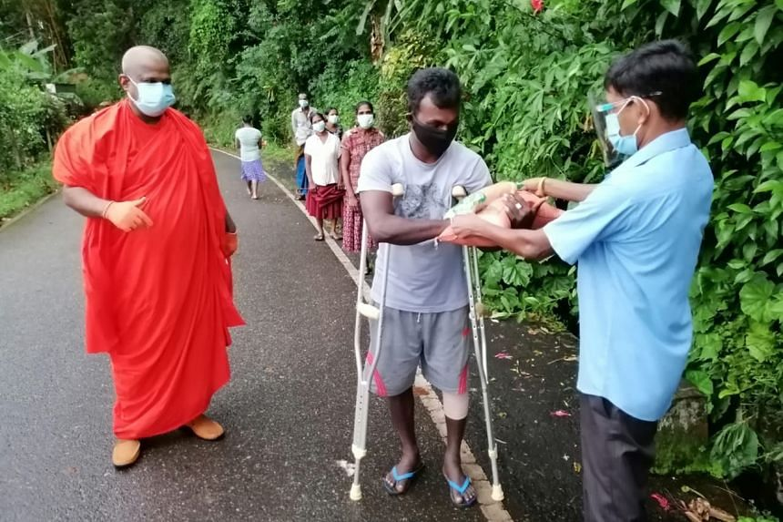 Sri Lankans receiving distributed food rations and masks.