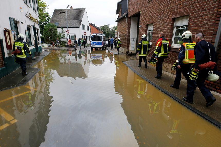 Firefighters walk along a flooded street following heavy rainfall in Erftstadt-Blessem, Germany, on July 16, 2021.