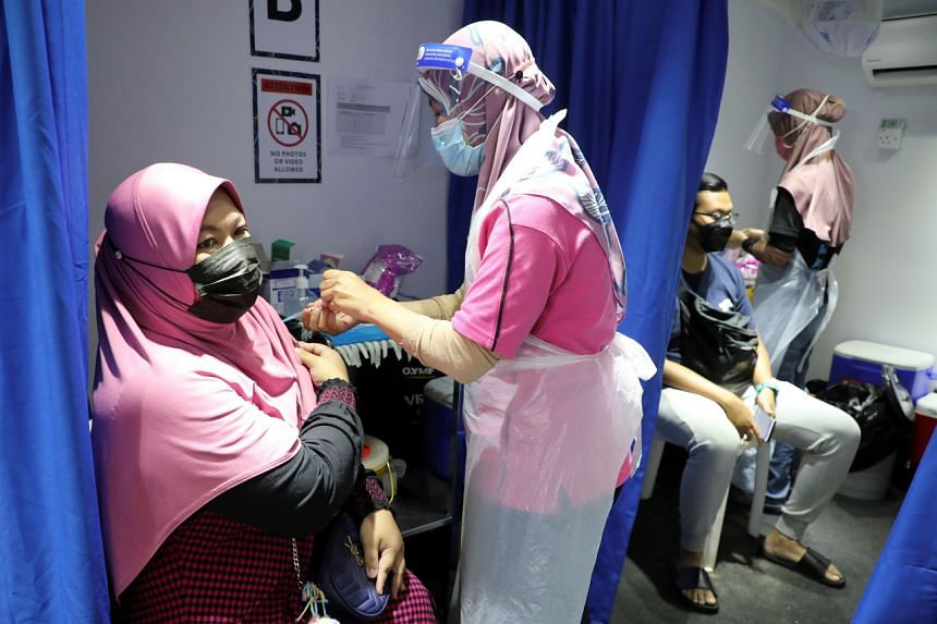 People receive the Sinovac Covid-19 vaccine in a vaccination truck in Kuala Lumpur, on July 12, 2021.