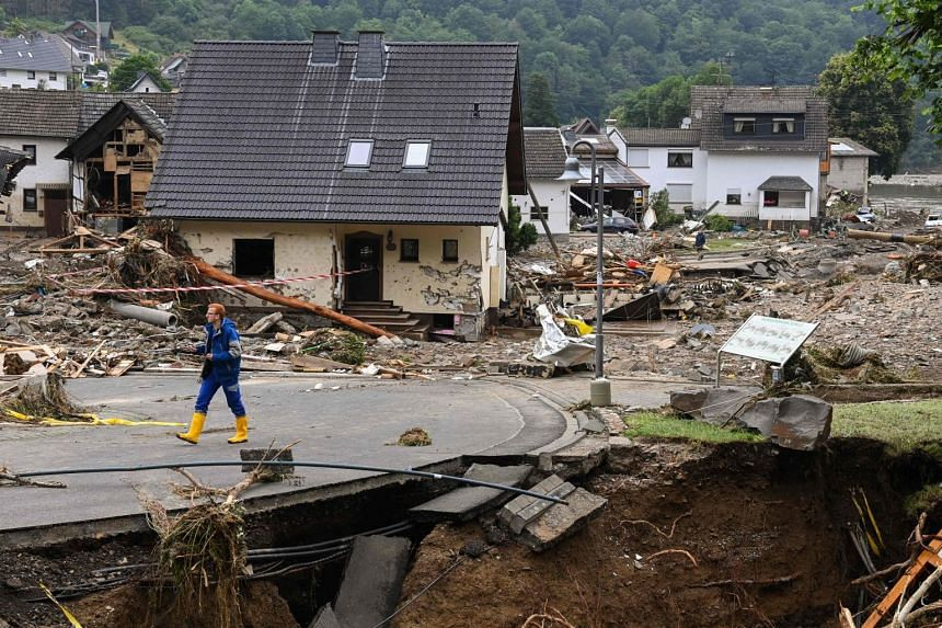 A man walks on a damaged road amid destroyed houses in Schuld, western Germany, on July 16, 2021.