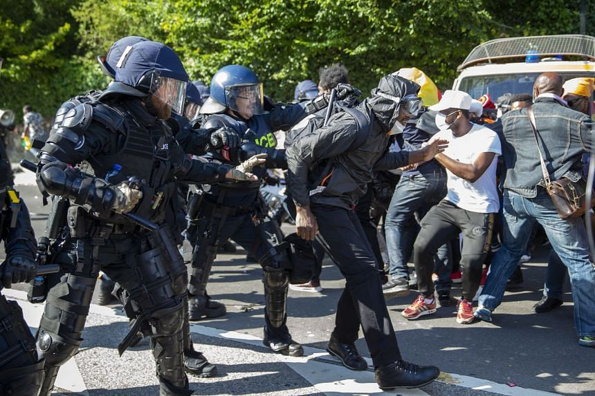 Swiss riot police clash with opponents of Cameroon's President Paul Biya outside his hotel in Geneva.