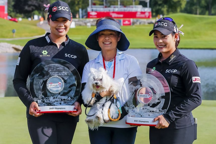 Thai sisters Ariya (left) and Moriya Jutanugarn and their mother Narumon posing with their trophies after winning the Dow Great Lakes Bay Invitational in Midland, Michigan on July 17, 2021.