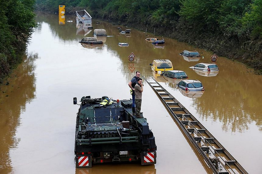 A police officer and a member of the German armed forces standing on a vehicle among partially submerged cars on a flooded road following heavy rain in Erftstadt-Blessem, Germany, yesterday. More than 130 people are dead and 1,300 unaccounted for aft