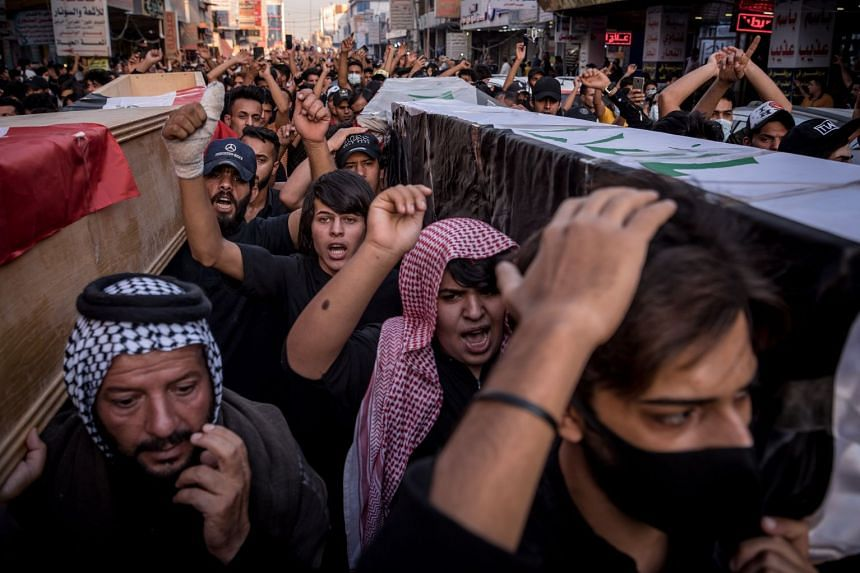 People chant slogans as they walk with mock coffins in Nasiriyah, Iraq, on July 15, 2021, protesting corruption following a fire in a coronavirus ward at Imam Hussein Teaching Hospital.
