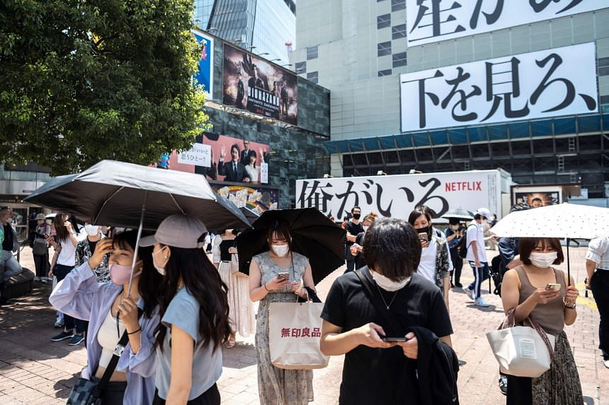 People using umbrellas to shield themselves from the sun in Tokyo last Monday. Adding to the Covid-19 crisis, hundreds of people in the Japanese capital were taken to hospital last week with heatstroke. Part of the Olympic Village in Tokyo built to h