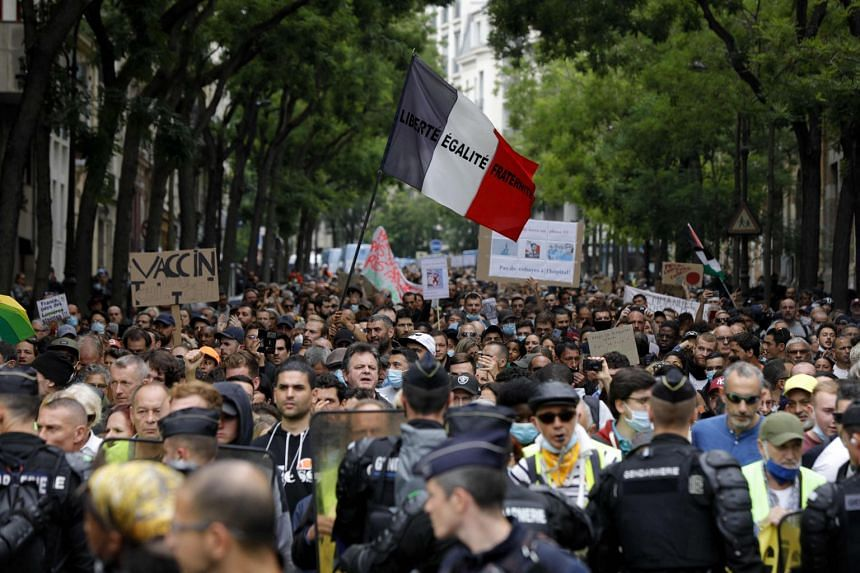 """Gendarmes stand in front of a protester holding a national flag reading """"Liberty Egality Fraternity"""" during a demonstration against new coronavirus safety measures in Paris, on July 17, 2021."""