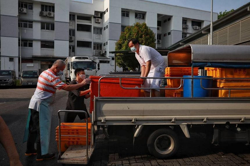 Fishmongers loading up boxes fish at Kovan 209 Market and Food Centre on July 18, 2021.