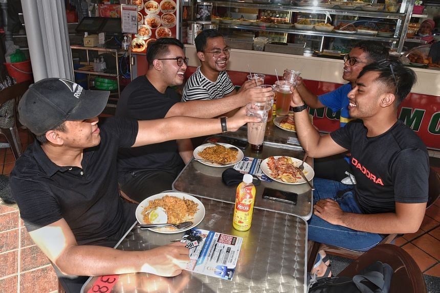 A group of former schoolmates catching up with one another over food and drinks at Kampong Glam Cafe on July 17, 2021.