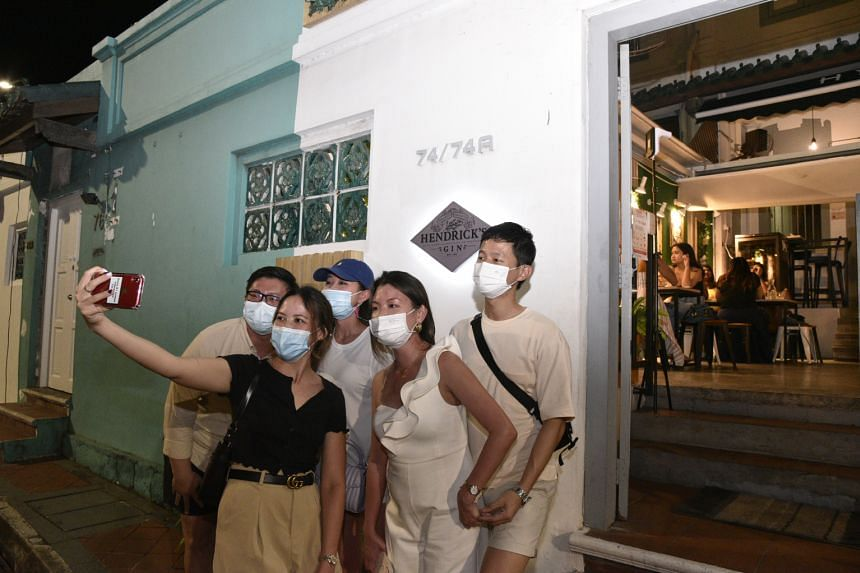 A group of five taking a wefie before entering cocktail bar and restaurant Jekyll & Hyde, located along Neil Road, on July 17, 2021.