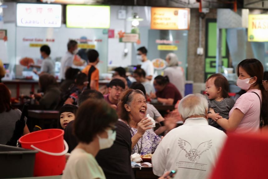 An elderly woman having a light-hearted moment while out for a meal with her family at a food court in Clementi Mall on July 15, 2021.