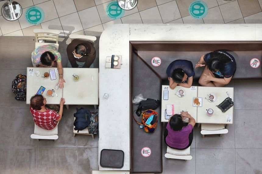 Two tables of patrons engaged in their own animated discussions during the lunch hour at the Toast Box outlet in Tampines 1 mall on July 16, 2021.