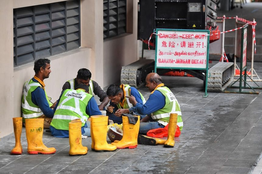 Construction workers having their lunch at a sheltered walkway in Balestier amid a heavy downpour on July 14, 2021.