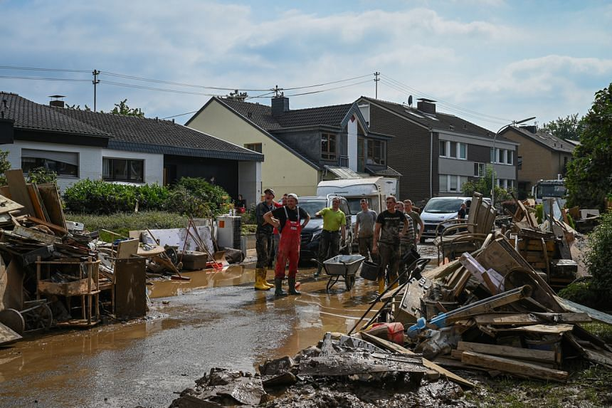 Volunteers clean the streets around the Lebenshilfe Haus care home in Sinzig, Germany, on July 17, 2021.