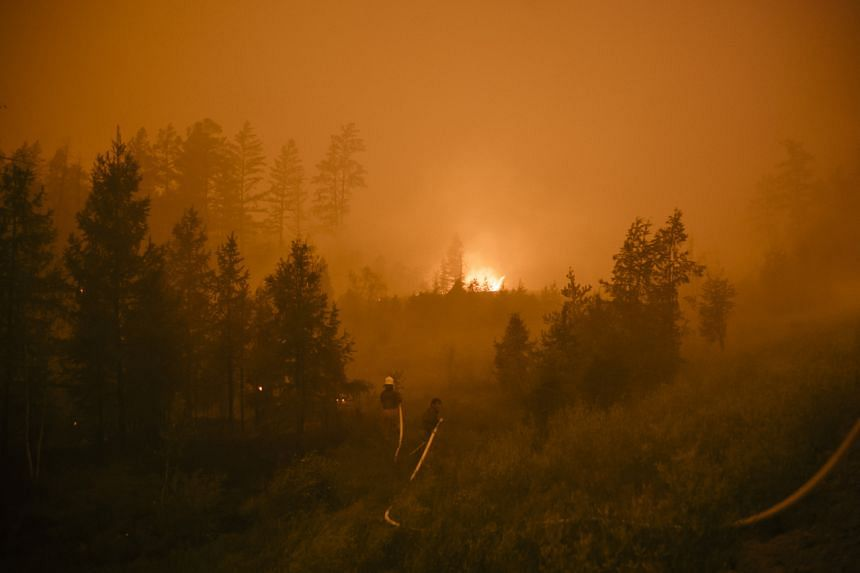 A forest fire burns on the road between Magaras and Berdigestyakh, west of Yakutsk, Russia, in July 2021.