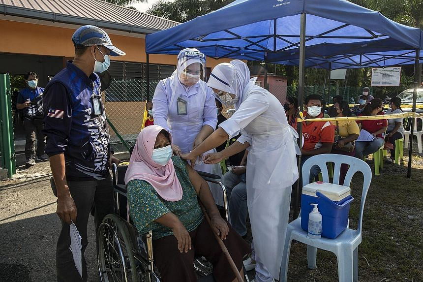 A woman receiving her Covid-19 vaccine jab as part of a vaccination outreach programme in Dengkil town, outside Kuala Lumpur, yesterday. Malaysia has administered over 14 million vaccine doses so far, with nearly 20 per cent of adults fully immunised