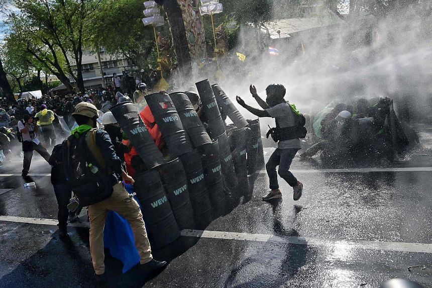 Protesters confronting riot police in Bangkok during a march from the Democracy Monument towards Government House, where Prime Minister Prayut Chan-o-cha works, yesterday.