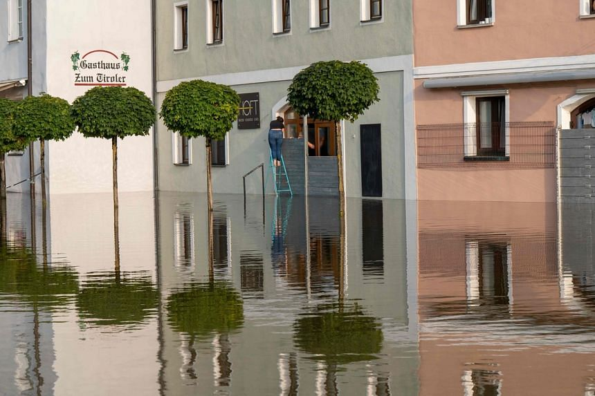 Two people seal the entrance of a cafe with a special flood barrier as water levels continue to rise in Passau, southern Germany, on July 18, 2021.