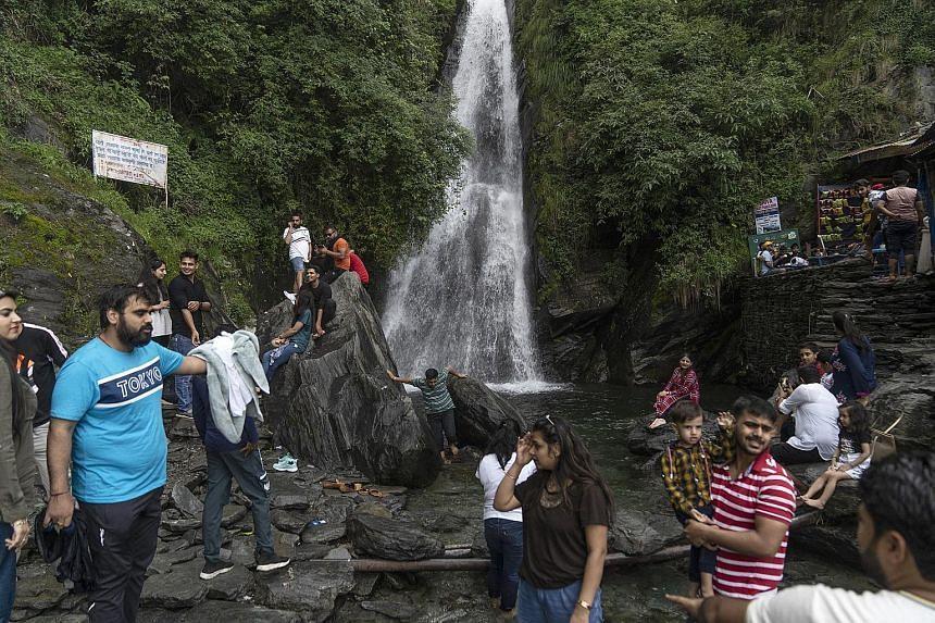 Tourists at Bhagsunag waterfall at Bhagsu village, in Dharamshala in India's Himachal Pradesh state, on July 1, 2021.