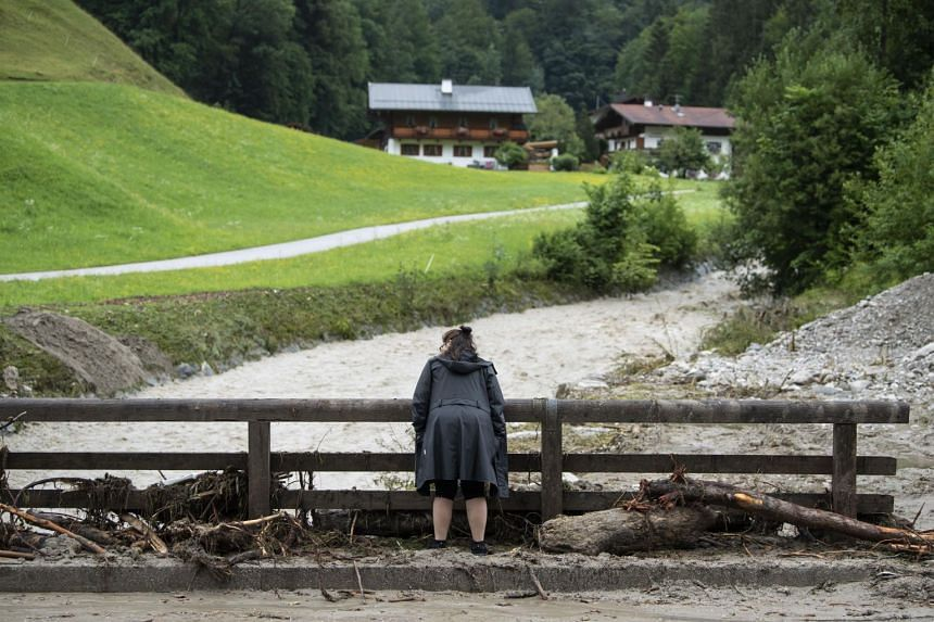 A woman stands among flood debris to look at a overflowing river in Markschellenberg near Berchtesgaden, Germany, on July 18, 2021.