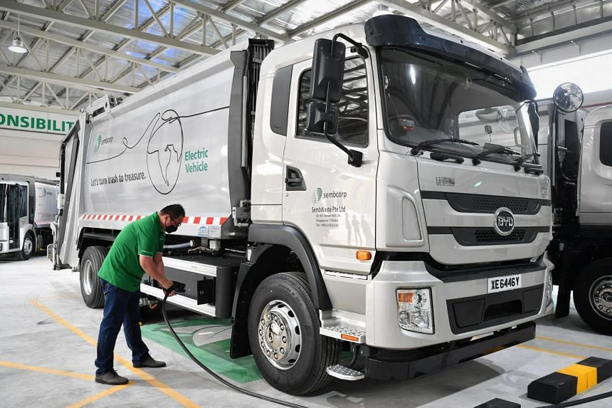 A worker charging a SembWaste refuse collection electric truck on July 19, 2021.