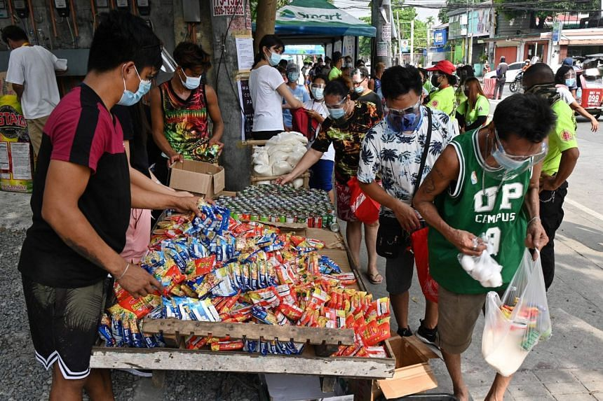 Residents collect free food packets from a community food bank in Quezon City, Manila, on April 21, 2021.