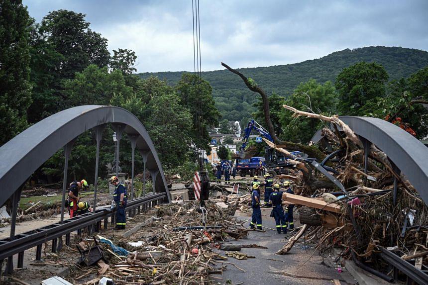 Workers clear debris from a damaged bridge in Bad Neuenahr-Ahrweiler, Germany, on July 19, 2021.