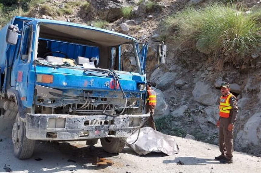 Pakistani rescue officials inspect the scene of a blast that targeted a bus carrying Chinese engineers to the site of Dasu Dam in Kohistan, Pakistan, on July 14 2021.