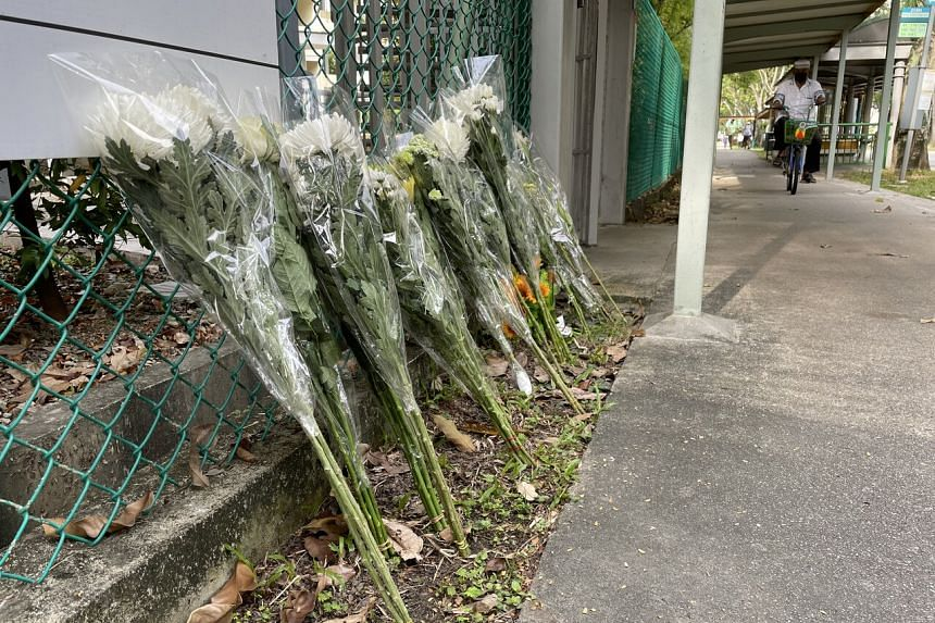 Bouquets of flowers placed at the back gate of River Valley High School on July 20, 2021.