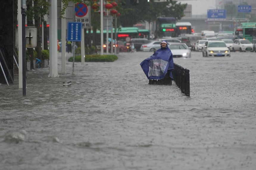 A resident wearing a rain cover stands on a flooded road in Henan, Zhengzhou province, on July 20, 2021.