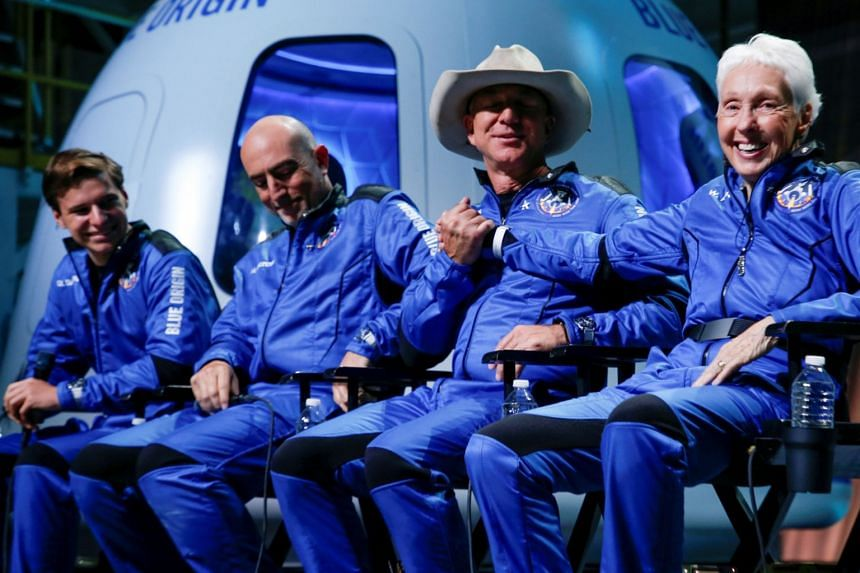 Jeff Bezos (third from left) shakes hands with Wally Funk as brother Mark Bezos (second from left) and Oliver Daemen (left) look on at a press conference after their flight into space.