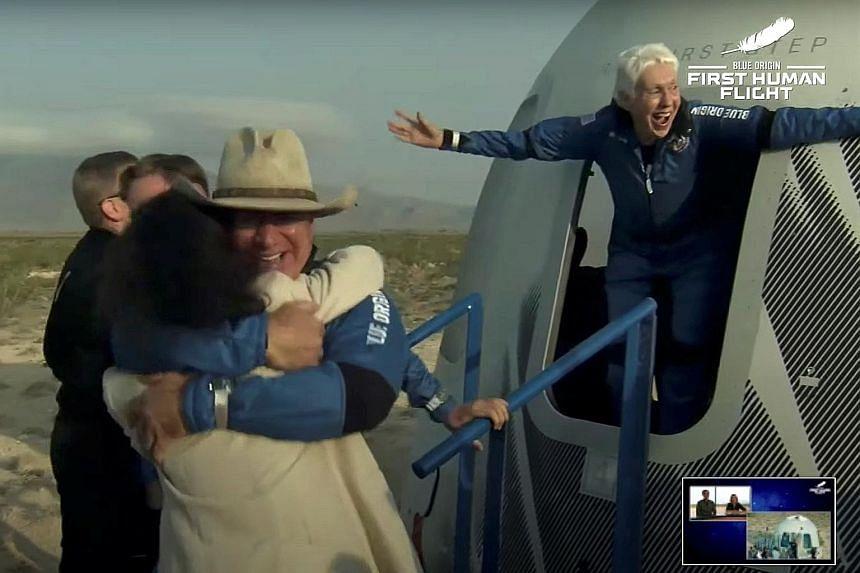 Left: The capsule carrying the crew returning to Earth via parachutes. Below: Mr Bezos (wearing hat) being welcomed on his return while pioneering female aviator Wally Funk emerges from the capsule. Billionaire Jeff Bezos and three crew members aboar