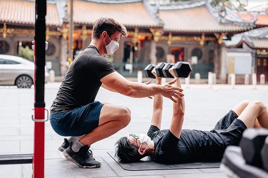 A fitness coach from Level Gym conducting a one-to-one training session. From tomorrow, mask-on activities can be conducted in groups of no more than two people, in classes of up to 30. PHOTO: LEVEL SINGAPORE