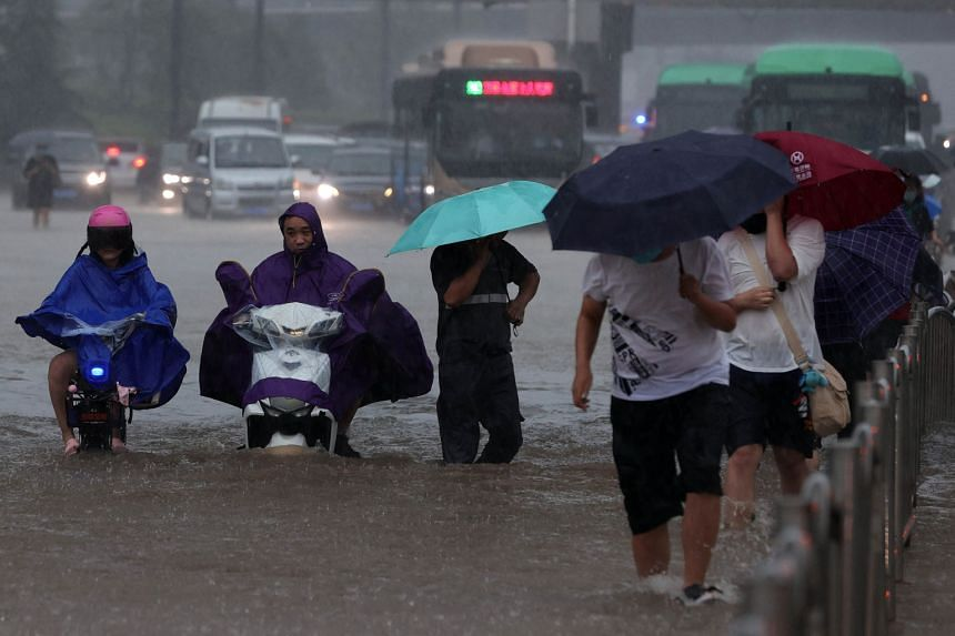 Residents wade through floodwaters on a flooded road amid heavy rainfall in Zhengzhou, Henan province on July 20, 2021.