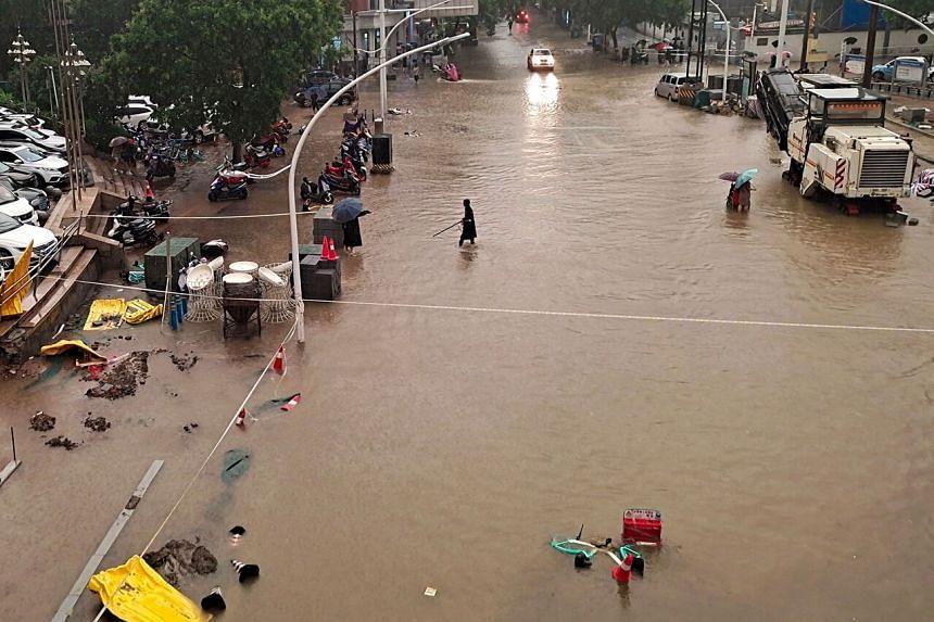 People wading through flood waters along a street following heavy rains in Zhengzhou on July 20, 2021.