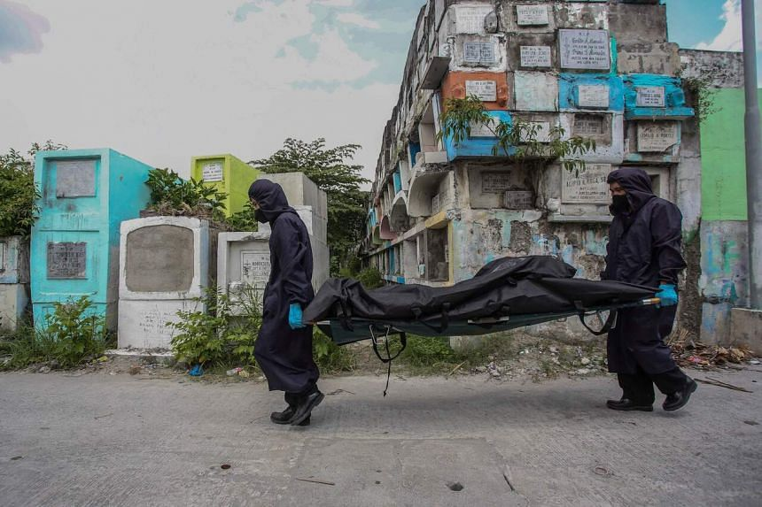 Workers wearing masks, gloves and protective coats as they carry a body bag containing the skeletal remains of Rodzon Enriquez on July 8, 2021.