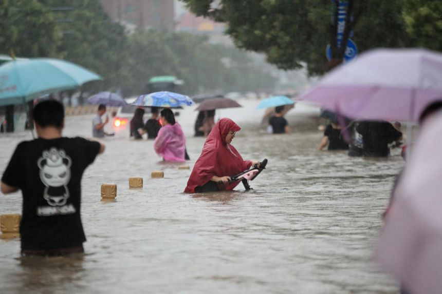 Residents wade through floodwaters in Zhengzhou, Henan province, China, on July 20, 2021.