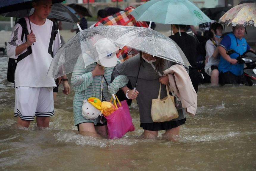 Residents wade through floodwaters on a road in Zhengzhou, Henan province, China, on July 20, 2021.