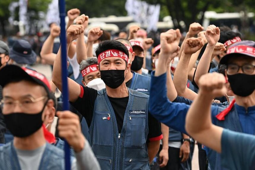 Thousands of parcel delivery workers shout slogans during a rally calling for improvement of working conditions in Seoul on June 15, 2021, as the delivery workers' union launched a general strike to call for implementation of an agreement on preventi