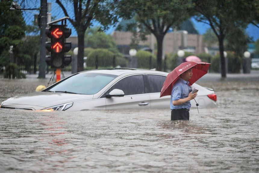 A man wading past a submerged car along a flooded street following heavy rains in Zhengzhou in China's central Henan province on July 20, 2021.