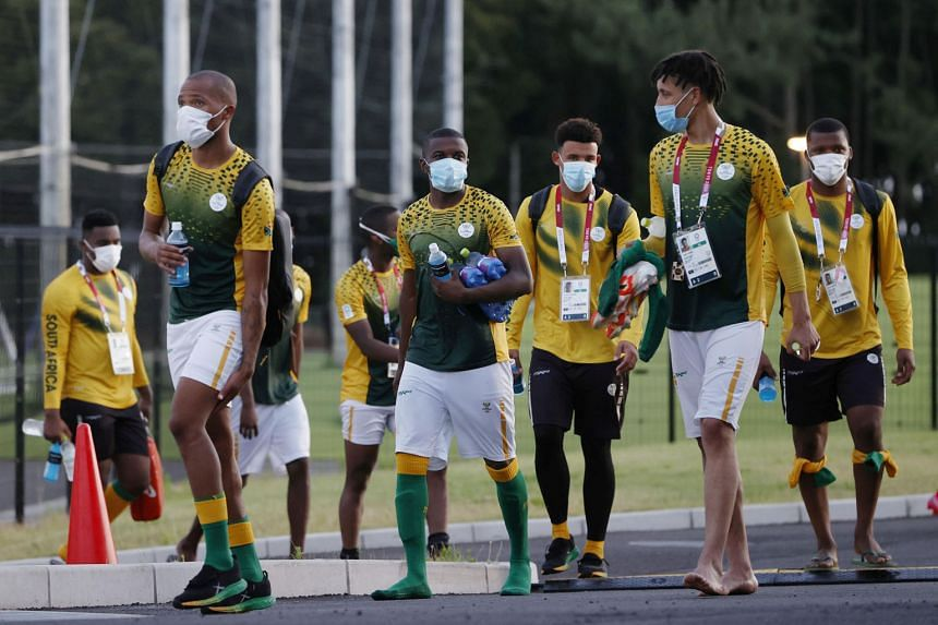 Members of South Africa's Olympic football team wearing masks and leaving after their training session in Chiba on Monday. They face hosts Japan tomorrow in their opener.