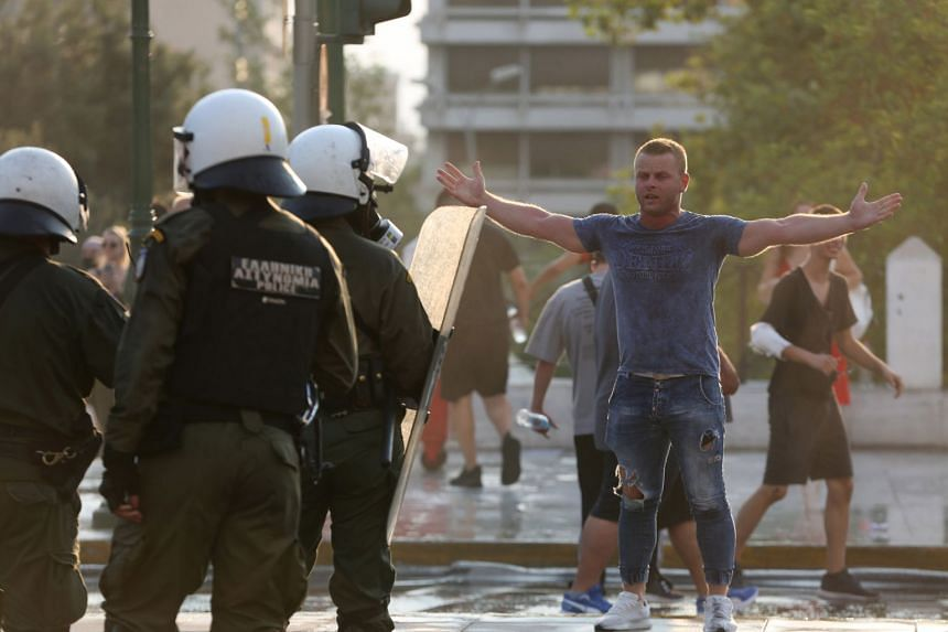 A protester gestures as riot police disperse the crowd during an anti-vaccine protest in Athens.