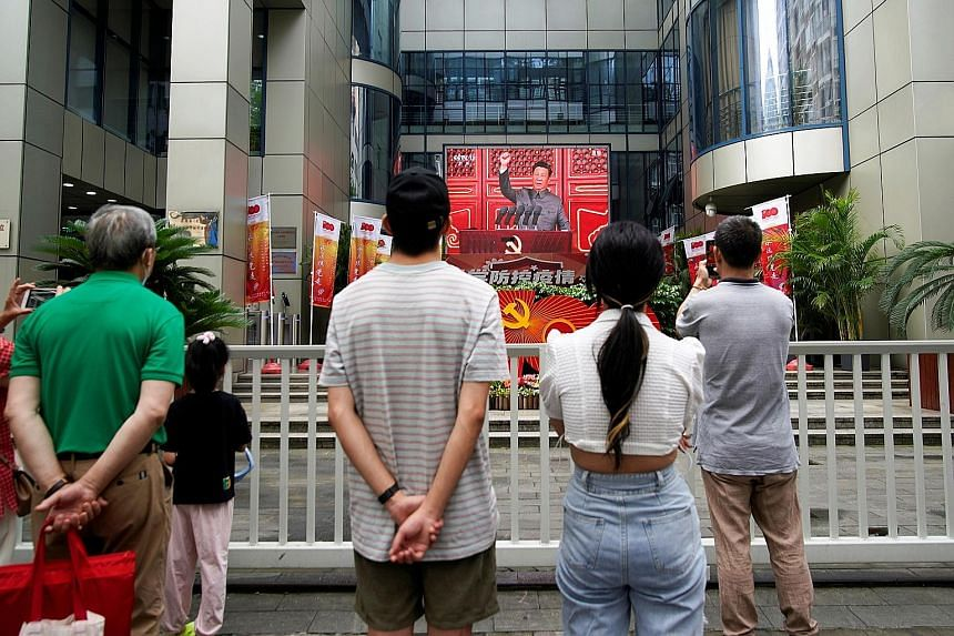 People in Shanghai watching a giant screen airing President Xi Jinping's speech at an event marking the 100th founding anniversary of the Communist Party of China on July 1. In his 70-minute speech, he said remaining loyal to the party and faithful t