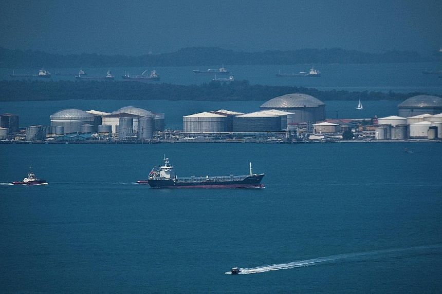Ships in the waters of the Singapore Strait near Pulau Sebarok, with its oil storage tanks, in April. Singapore is the dominant marine fuel supplier in Asia, but China is catching up.