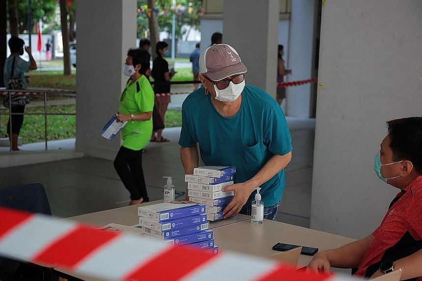 A resident collecting free antigen rapid test kits at Block 5 Haig Road in Geylang yesterday. The Ministry of Health worked with the People's Association to distribute the self-test kits as an added layer of ring-fencing to help identify Covid-19 cas