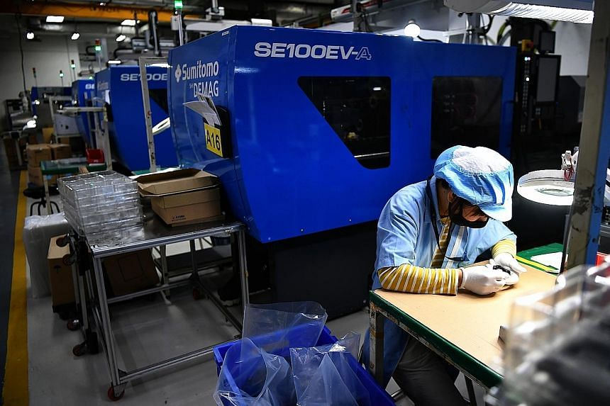 A worker at plastics manufacturer Sanwa Plastic examining a product in the production area. Manufacturing is one of the sectors that are not likely to see much impact from tightened Covid-19 measures. ST PHOTO: LIM YAOHUI