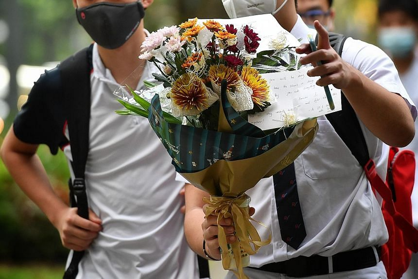 Many students of River Valley High School turned up yesterday with flowers, which they left at the school foyer (top) to pay tribute to their 13-year-old schoolmate who was allegedly murdered on Monday. ST PHOTOS: CHONG JUN LIANG