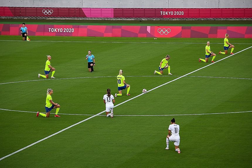 Players taking the knee to highlight racial injustice ahead of the women's football match between the United States and Sweden yesterday. It is the first time the gesture has been seen at an Olympics.