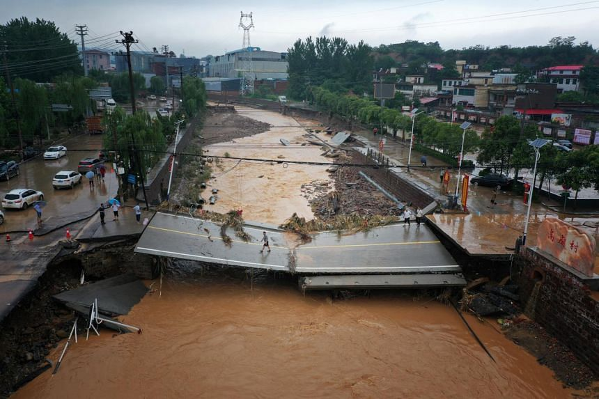 An aerial view shows cars sitting in floodwaters at the entrance of a tunnel after heavy rains hit Zhengzhou, Henan, on July 22, 2021.
