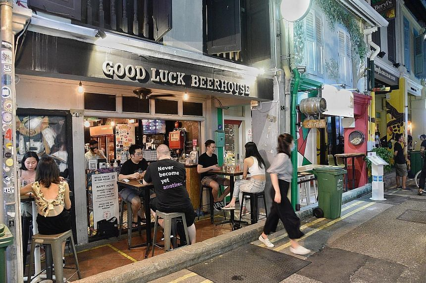 Diners outside Good Luck Beerhouse at Haji Lane yesterday before new restrictions kick in today.